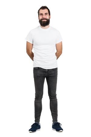 jeans apretados: hombre de la barba feliz con las manos detrás de la espalda de la camiseta blanca y pantalones vaqueros apretados mirando a la cámara. la longitud del cuerpo Retrato completo aislado sobre fondo blanco del estudio.
