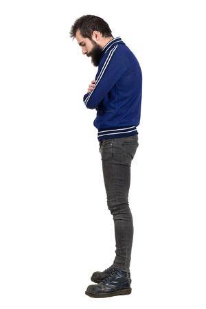 Profile view of bearded hipster in blue tracksuit jacket looking down with crossed arms. Full body length portrait isolated over white studio background.