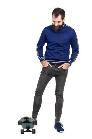 jeans apretados: Sonriendo inconformista seguro que lo lleva chaqueta de chándal azul y pantalones vaqueros ajustados de pie en el patín. la longitud del cuerpo Retrato completo aislado sobre fondo blanco del estudio. Foto de archivo