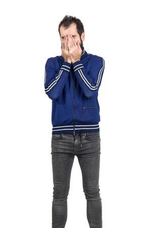 tracksuit: Bearded young man covering face with his hands laughing. Standing portrait isolated over white studio background.