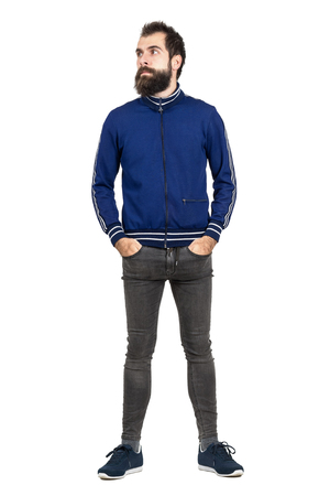 tight jeans: Serious bearded hipster in tracksuit jacket with hands in pockets looking away. Full body length portrait isolated over white studio background. Stock Photo