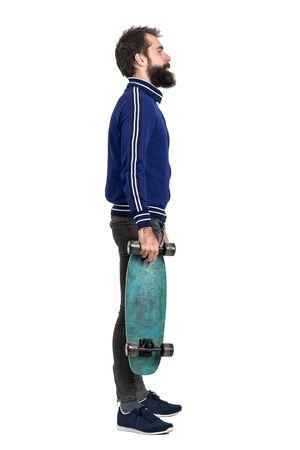 jeans apretados: Vista lateral de la joven inconformista barba en la chaqueta de chándal llevar monopatín. la longitud del cuerpo Retrato completo aislado sobre fondo blanco del estudio.
