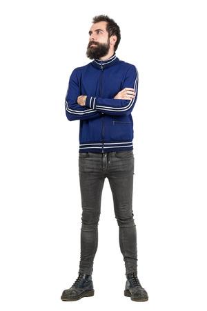 mani incrociate: Tirante duro con la barba che indossa giacca tuta e jeans con le braccia incrociate in cerca di distanza. Tutto il corpo ritratto di lunghezza isolato su sfondo bianco studio. Archivio Fotografico