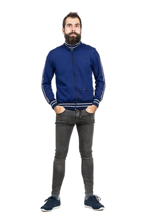 tracksuit: Serious bearded hipster with hands in pockets in old fashioned clothes looking at camera. Full body length portrait isolated over white studio background.