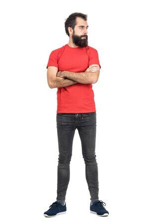 jeans apretados: barbudo joven en rojo camiseta con los brazos cruzados mirando a otro lado. la longitud del cuerpo Retrato completo aislado sobre fondo blanco del estudio.