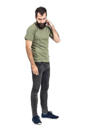 tight jeans: hombre joven con barba que rascarse la cabeza mirando hacia abajo vista lateral. la longitud del cuerpo Retrato completo aislado sobre fondo blanco del estudio.