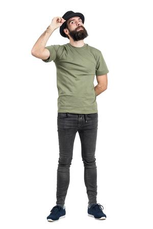 hombre con sombrero: Hombre que ajusta el sombrero con la cabeza se inclinó hacia atrás mirando a la cámara intensa. la longitud del cuerpo Retrato completo aislado sobre fondo blanco del estudio.