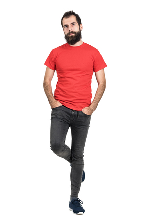 jeans apretados: inconformista barbudo en la camiseta roja de pie y mantener el equilibrio sobre una pierna mirando a otro lado. la longitud del cuerpo Retrato completo aislado sobre fondo blanco del estudio.