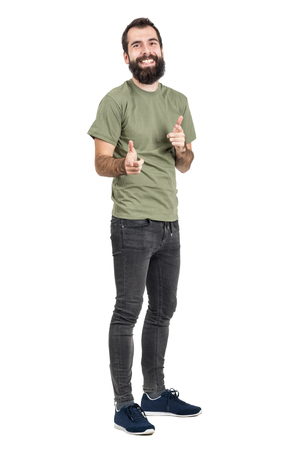 skinny: Espontáneamente se ríe el hombre de barba con los dedos apuntando camiseta verde a la cámara. la longitud del cuerpo Retrato completo aislado sobre fondo blanco del estudio.
