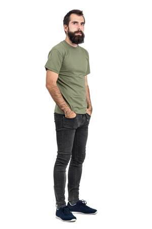 Serious bearded man with hands in pockets looking at camera. Full body length portrait isolated over white studio background.
