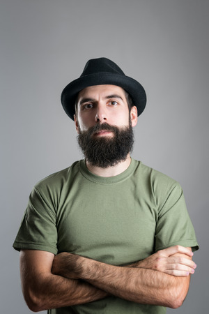 serious guy: Serious confident bearded guy with crossed arms looking at camera.  Headshot portrait over gray studio background with vignette.