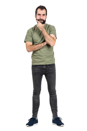 funny bearded man: Young bearded man in green t-shirt touching his beard looking at camera. Full body length portrait isolated over white studio background.