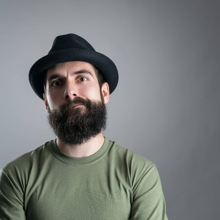 distrustful: Skeptical bearded hipster staring at camera.  Headshot close up portrait over gray studio background with vignette.