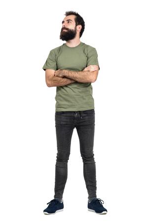 jeans apretados: hombre de la barba orgullosa confianza con los brazos cruzados mirando hacia arriba. la longitud del cuerpo Retrato completo aislado sobre fondo blanco del estudio.