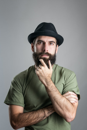 guys: Front view of thoughtful man stroking his beard looking at camera.  Headshot portrait over gray studio background with vignette.