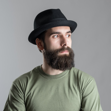 pensive: Serious pensive bearded man looking away.  Headshot close up portrait over gray studio background. Stock Photo