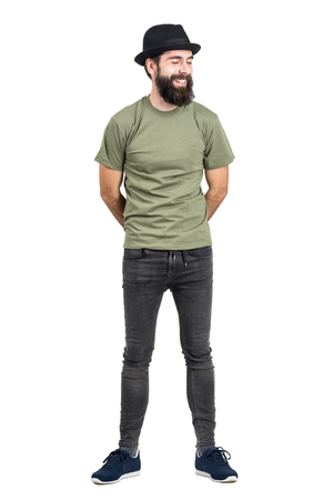 tight jeans: Bearded man wearing hat and t-shirt laughing carefree with eyes closed. Full body length portrait isolated over white studio background.