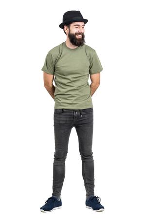 jeans apretados: Hombre barbudo que lleva el sombrero y camiseta de risa despreocupada con los ojos cerrados. la longitud del cuerpo Retrato completo aislado sobre fondo blanco del estudio.