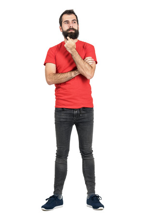 uomo rosso: pantaloni a vita bassa barbuto pensare e di toccare la barba cercando di distanza. Tutto il corpo ritratto di lunghezza isolato su sfondo bianco studio. Archivio Fotografico