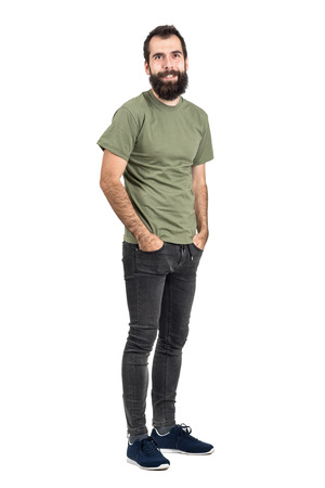 tight jeans: Happy smiling bearded hipster with hands in pockets. Full body length portrait isolated over white studio background. Foto de archivo