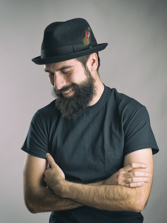 spontaneous: Bearded hipster wearing black t-shirt and hat laughing spontaneous looking down. Retro toned filtered portrait over gray background with vignette effect.