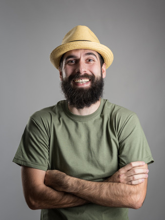 looking to camera: Spontaneously hard laughing bearded man wearing straw hat looking at camera.  Headshot portrait over gray studio background with vignette. Stock Photo