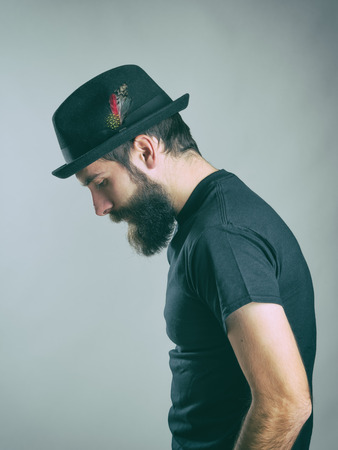 side effect: Side view of sad hunched bearded man with hat looking down. Retro toned filtered portrait over gray background with vignette effect.