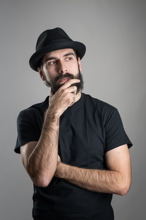 stroking: Thinking hipster wearing black t-shirt and hat stroking beard looking away.  Headshot portrait over gray studio background with vignette.