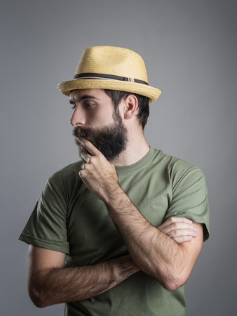 straw hat: Profile view of young pensive bearded man wearing straw hat touching his beard. Headshot portrait over gray studio background with vignette. Stock Photo