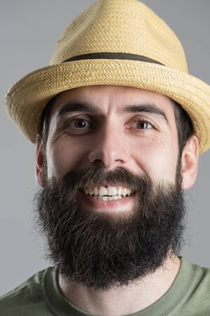 headshot: Close up portrait of laughing bearded man in straw hat looking at camera. Headshot over gray studio background.