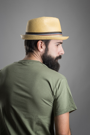 headshot: Rear view of young serious bearded man with straw hat looking away. Headshot portrait over gray studio background with vignette. Stock Photo
