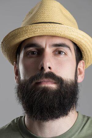 Close up Portrait von zuversichtlich stolz Hipster mit Strohhut in die Kamera. Kopfbild über grau Studio Hintergrund.