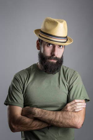 scowl: Serious unhappy bearded man with straw hat intense scowl at camera. Headshot portrait over gray studio background with vignette.