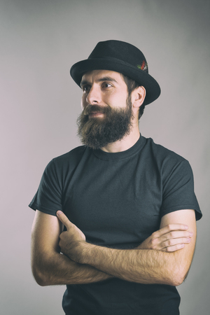 Portrait of happy bearded man with crossed arms looking away. Retro toned filtered portrait over gray background with vignette effect. Stock Photo