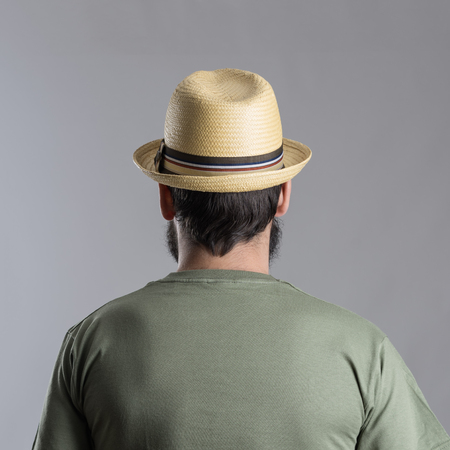headshot: Back view of bearded man with straw hat looking away.  Headshot portrait over gray studio background. Stock Photo