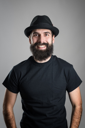headshot: Laughing bearded hipster wearing black t-shirt and hat looking at camera.  Headshot portrait over gray studio background with vignette.
