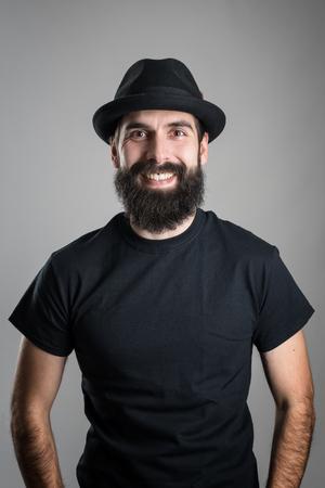 jovenes felices: Riendo inconformista barba que lleva negro camiseta y sombrero mirando a la cámara. Retrato de vieron sobre fondo gris del estudio con la ilustración.