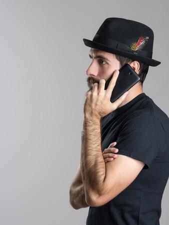 hablando por telefono: Vista lateral del hombre joven con barba pensativo que habla en el teléfono que mira lejos sobre fondo gris de estudio Foto de archivo