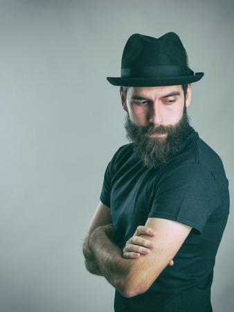 Zijaanzicht van de droevige gebaarde stijlvolle man draagt hoed terug te kijken over de schouder. Retro stijl afgezwakt gefilterd vintage foto met vervaagde kleuren.