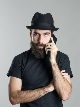 young guy: Front view portrait of bearded hipster wearing black hat and t-shirt talking on the phone looking at camera over gray studio background