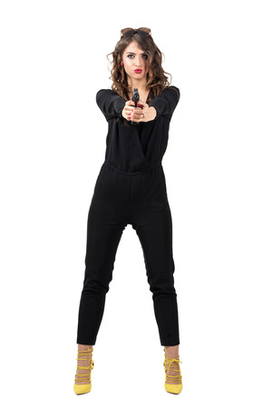 Tough sexy woman in black overalls pointing pistol at camera. Full body length portrait isolated over white studio background.