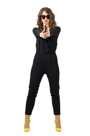 mobster: Dangerous mobster woman with sunglasses aiming handgun at camera. Full body length portrait isolated over white studio background.