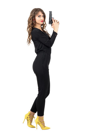 gangster girl: Side view of dangerous female carrying a weapon looking at camera. Full body length portrait isolated over white studio background. Stock Photo