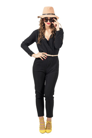 jumpsuit: Sensual fashion woman wearing hat with look over sunglasses. Full body length portrait isolated over white studio background.