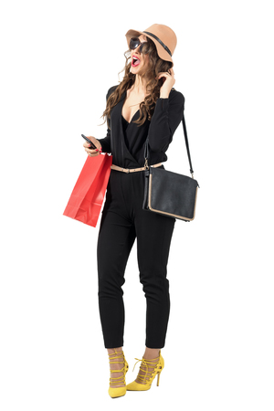isolated woman: Excited trendy shopping woman wearing paper bag looking away. Full body length portrait isolated over white studio background.