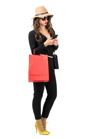 jumpsuit: Trendy modern shopping woman carrying bag typing on the smartphone. Full body length portrait isolated over white studio background. Stock Photo