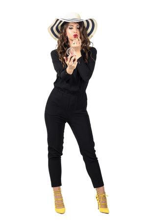 standing up: Gorgeous fashion beauty in black overalls wearing summer hat fixing makeup. Full body length portrait isolated over white studio background.