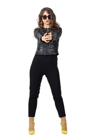 aiming: Dangerous tough female spy in leather jacket with sunglasses aiming gun at camera. Full body length portrait isolated over white studio background. Stock Photo