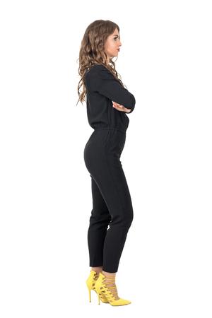 tacones negros: Belleza confidente del modelo de manera con los brazos cruzados en visión lateral de los guardapolvos negros. Retrato de longitud completa del cuerpo aislado sobre fondo blanco del estudio.