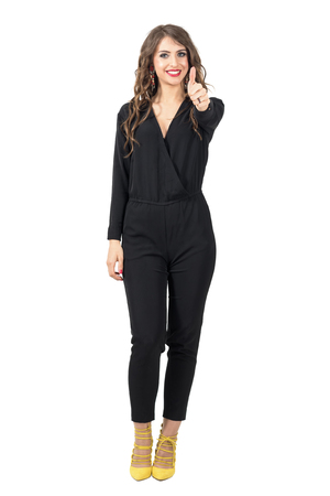 jumpsuit: Beautiful fashion model in black jumpsuit with thumb up gesture. Full body length portrait isolated over white studio background.